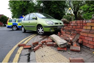 car crashed into brick wall